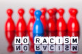 Cube letters in front of unsharp ludo figures show no racism colorful Royalty Free Stock Photos