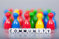 Cube letters show community in front of unsharp ludo figures background is light gray Royalty Free Stock Photos