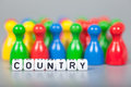 Cube letters show country in front of unsharp ludo figures background is light gray Stock Photo