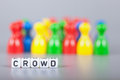 Cube letters show crowd in front of unsharp ludo figures background is light gray Royalty Free Stock Image