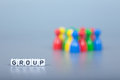 Cube letters show group in front of unsharp ludo figures background is light gray Stock Photography