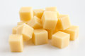 Cubes of yellow cheese stacked randomly on white Stock Photos