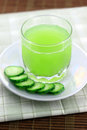 Cucumber juice next to slices Stock Photography