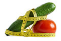 Cucumber and tomato with measuring tape over white the concept of dieting health Stock Photography