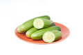 Cucumbers in brown plate on white Royalty Free Stock Photo