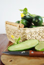 Cucumbers with a cutting board on the table Stock Photos