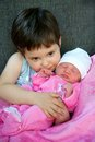 Cuddling a young boy his newborn baby sister Stock Image