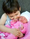 Cuddling a young boy his newborn baby sister Royalty Free Stock Photos