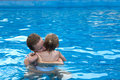 Cuddly in the pool mother and daughter cuddling with copy space on right Stock Photography