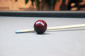 Cue on a grey billiard table and red ball cloth d Royalty Free Stock Photos