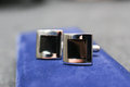 Cufflinks a pair of on blue stand Royalty Free Stock Photo