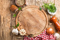 Culinary background with empty cutting board and spices on wooden table Royalty Free Stock Photos