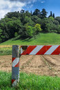 Cultivated field a red and white barrier blocks access to a Royalty Free Stock Photo