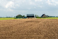 Cultivated soil in front of a modern Dutch farmhouse with barns Royalty Free Stock Photo