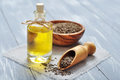Cumin oil in a glass bottle with seeds on wooden background Stock Photo
