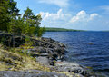 Cumulus clouds and stony shore of Ladoga lake Royalty Free Stock Image
