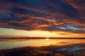 Cumulus sunset clouds with sun setting down. Fiery orange sunset sky. Beautiful sky. Royalty Free Stock Photo