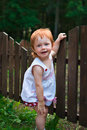 Cunning girl little playing near the fence Stock Image