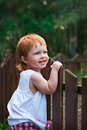 Cunning girl little playing near the fence Royalty Free Stock Images