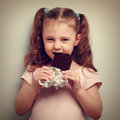 Cunning kid girl eating dark chocolate with pleasure and curious look vintage closeup portrait Royalty Free Stock Image