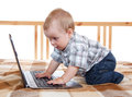 Cunning little boy works at his notebook on the bed Stock Photo