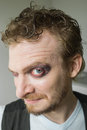 Cunning man with red painted eyes looks Stock Images