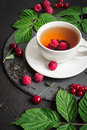 Cup of Berry tea and ripe raspberry, cherry, currant on a black background Royalty Free Stock Photo