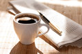 Cup of black coffee, newspaper and a pen against Royalty Free Stock Photo