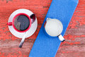 Cup of black coffee on a rustic red picnic table freshly brewed in mug white saucer served with jug milk and blue napkin grunge Royalty Free Stock Photography