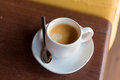 Cup of black coffee with spoon and saucer on table Royalty Free Stock Photo