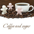 Cup of black coffee and sugar in the form of little men isolated on white Stock Photo