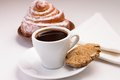 Cup of black coffee with a sweet bun and cookie on white plate rye Royalty Free Stock Images