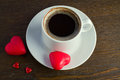 Cup of black coffee two marzipan red candy for valentine s day Royalty Free Stock Images