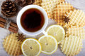 Cup of black tea with Christmas decor, lemon, pinecone, waffles, badian and cinnamon Royalty Free Stock Photo