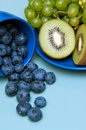 Cup of blueberries a kiwis and grapes knocked on the table Stock Photos