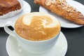 Cup of caffe latte with pastry almond croissant in background Stock Photo