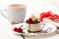 Cup cake and coffee with cream with raspberry chocolate in white plate on wooden white table near lie serviet whith spoon Royalty Free Stock Images