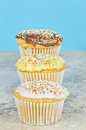 Cup cakes three cupcakes tiered with different toppings on a tile with a blue background Royalty Free Stock Photo