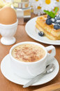 Cup of cappuccino belgian waffles with blueberries and egg for breakfast closeup Royalty Free Stock Image
