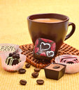 Cup of cappuccino with chocolate sweets and coffee beans on the tablecloth Stock Images