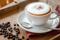 A cup of cappuccino beside with coffee beans Royalty Free Stock Photography