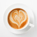 Cup of cappuccino coffee with a heart shape in the milky foam on top viewed from above in generic white and saucer on white Royalty Free Stock Photography