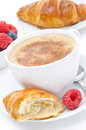 Cup of cappuccino and fresh croissant raspberry for breakfast selective focus vertical Stock Image