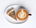 Cup of cappuccino and a piece of cake. Latte art. Isolated on white Royalty Free Stock Photo