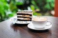 Cup of capuchino coffee with chocolate banana cake apuchino on a table close to nature Stock Photography