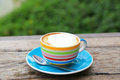 A cup of Capuchino coffee in a colorful cup on wooden background Royalty Free Stock Images