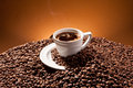 A cup and coffe beans brown background Royalty Free Stock Photo