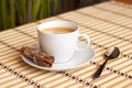 Cup of coffee on bamboo tablecloth with cinnamon sticks Stock Images