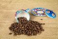 Cup with coffee beans colored plate and spilled Royalty Free Stock Photography