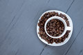 Cup with coffee beans inside on grey wooden background